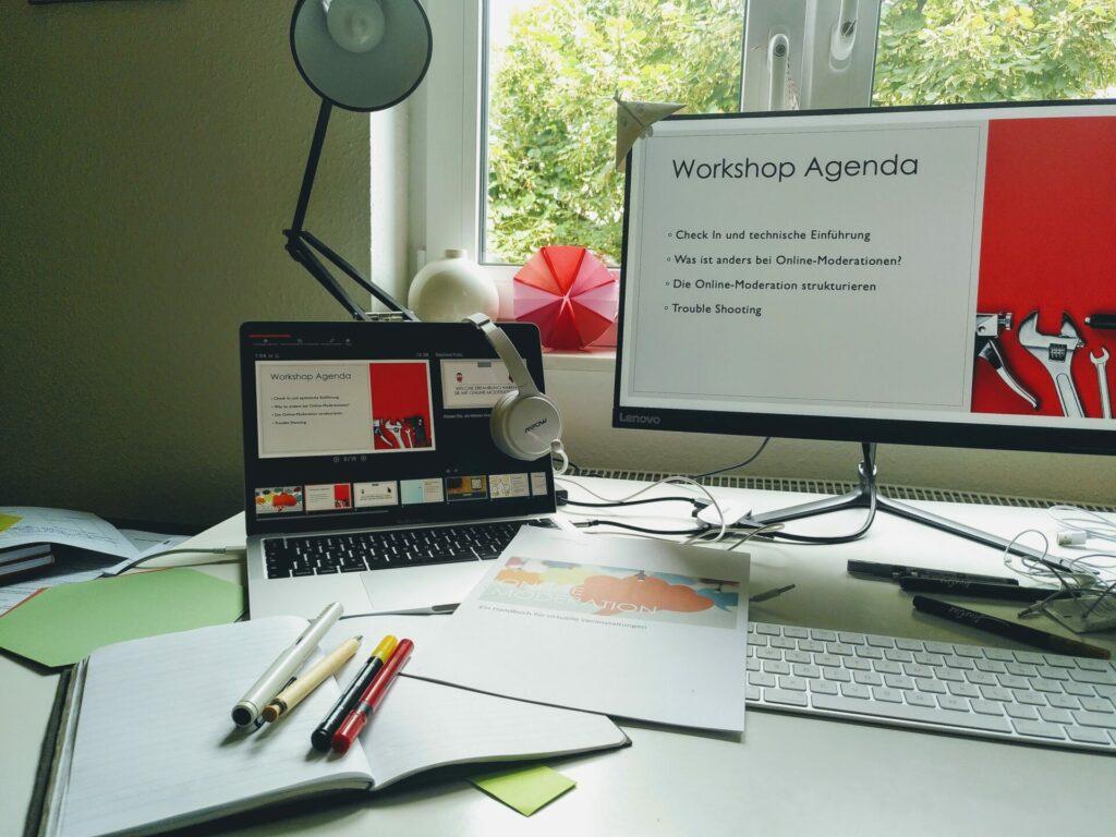 Schreibtisch mit Laptop, Bildschirm, Papieren